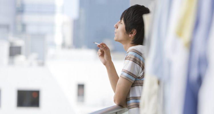 ベランダで喫煙する男性